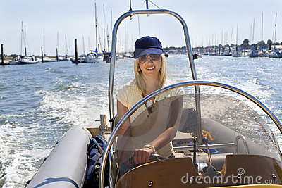 Beautiful Young Blond Woman Driving A Speedboat