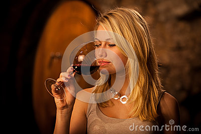 Beautiful young blond woman tasting red wine in a wine cellar Stock Photo