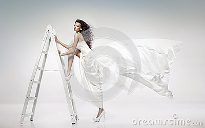Beautiful young bride holding the ladder