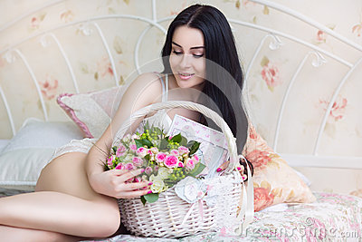 Beautiful young bride in a white dress with a wedding bouquet of
