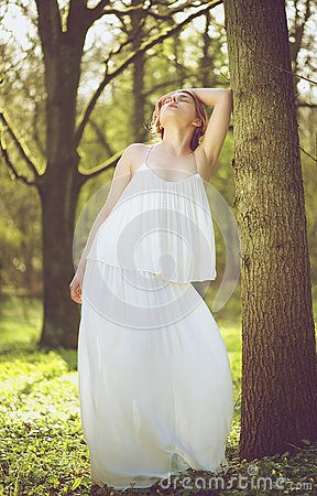 Beautiful young bride in white wedding dress posing against tree