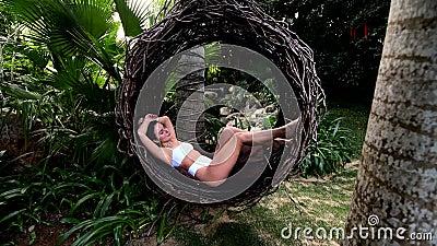 Beautiful young caucasian woman in air swingl at tropical park in asia, bali stock video