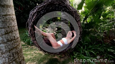 Beautiful young caucasian woman in air swingl at tropical park in asia, bali stock video footage