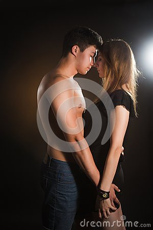 Beautiful young couple hugging and kissing isolated on black background.
