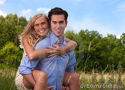 Beautiful, young couple piggybacking in tall grass