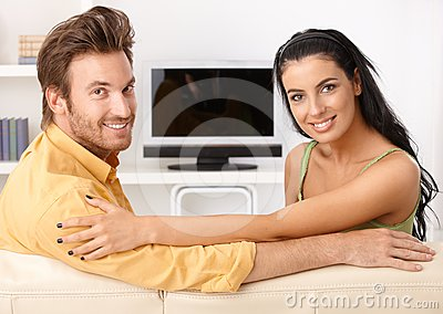 Beautiful young couple smiling on sofa