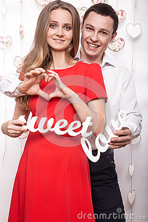 Free Beautiful Young Couple With Words Sweet Love Showing The Form Of Heart Hands. Valentine S Day. Stock Image - 65958371