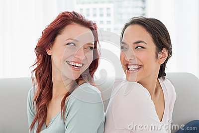 Beautiful young female friends sitting back to back at home