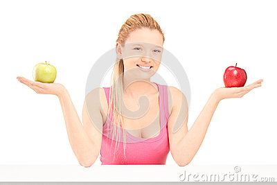 Beautiful young female sitting and holding apples in both hands