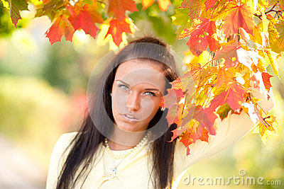 Beautiful young girl with autumn leaves