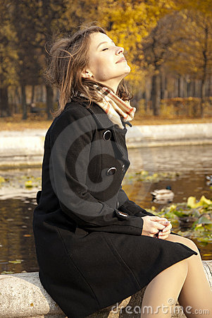 Beautiful young girl enjoying autumn sun
