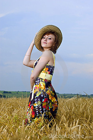 Beautiful young girl is in the field of wheat