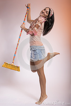 Young woman dancing with a broom