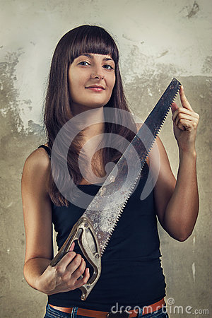 Beautiful young girl holding saw over grunge