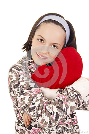 Beautiful young girl hugging heart shape pillow