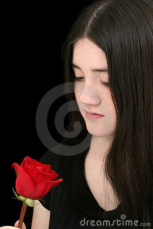Beautiful Young Girl Looking At Red Rose Against Black