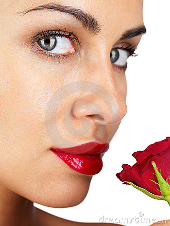 Beautiful young girl looking at you with red rose