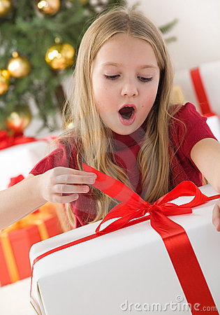 Beautiful young girl opening her christmas present