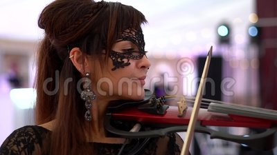 Beautiful young girl playing on electric violin on beautiful concert hall. In a beautiful evening dress. Clouse-up stock footage