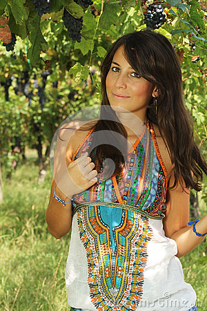Beautiful young girl posing in a vineyard