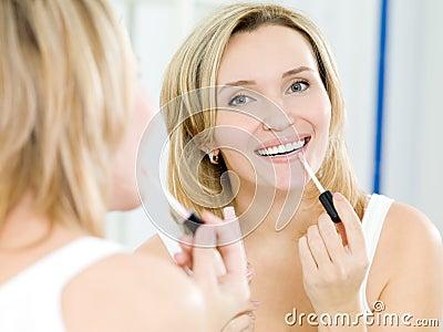 Beautiful young girl puts a lip gloss