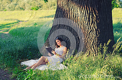Beautiful young girl reading book while sitting under giant oak Stock Photo