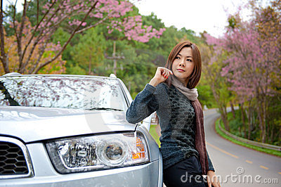 Beautiful young girl resting at side of her car