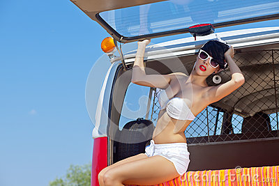 A beautiful young girl in retro look with a white swimsuit, a ba