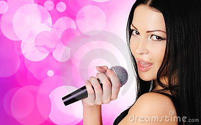 Beautiful young girl singing in microphone