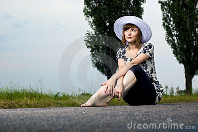Beautiful young girl sits in a hat
