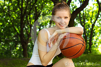 Beautiful young girl with a smile, sitting with a basketball ball in for sports