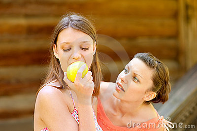 Beautiful young girl taking a bite of an apple