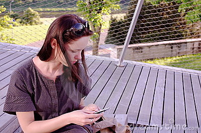 Beautiful young girl is typing sms near barber