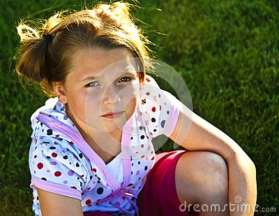 Beautiful young girl unhappy on the grass
