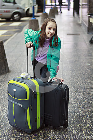 Beautiful young girl waiting with two suitcases