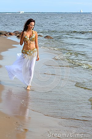 Beautiful young girl walking on beach