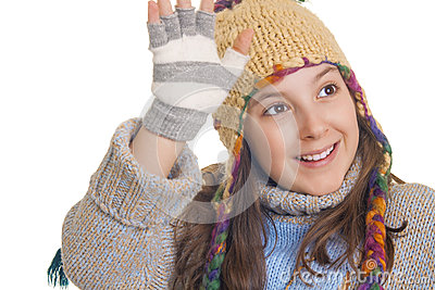 Beautiful young girl in warm winter clothes smiles and waving