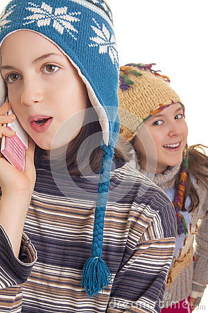 Beautiful young girl in warm winter clothes speaking on a mobile