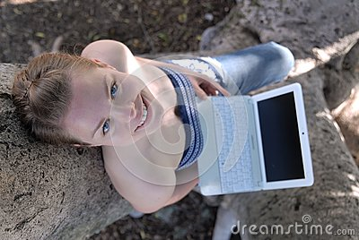 Beautiful young girl working with laptop in tree