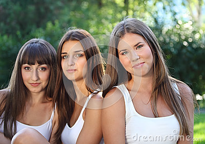 Beautiful young girls in green summer park