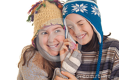 Beautiful young girls in warm winter clothes speaking on a mobil