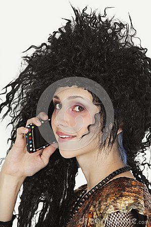 Beautiful young Goth woman with teased hair using mobile phone