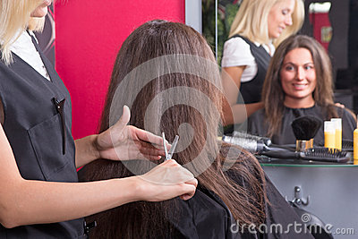Beautiful young hairdresser giving a new haircut to female custo