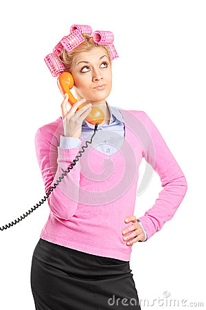 Beautiful young housewife with hair rollers talking on a phone