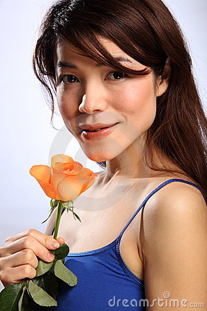 Beautiful young Japanese girl with orange rose