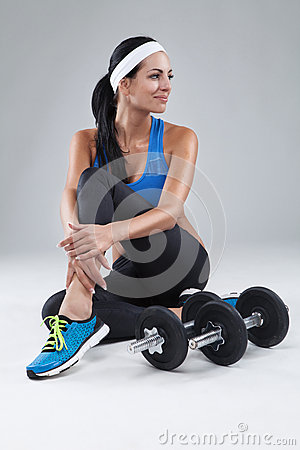 Beautiful young jogging woman exercises with dumbbells Isolated