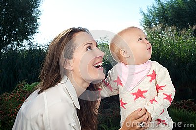 Beautiful young mother looking away with cute baby outdoors