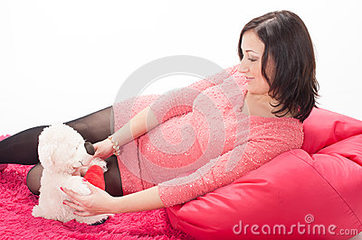 Beautiful young pregnant woman holding a teddy bear toy