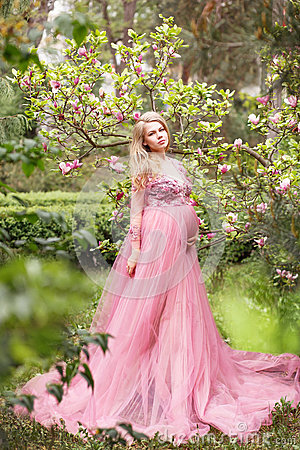 Free Beautiful Young Pregnant Woman In A Long Sexy Pink Dress Standing Near A Blooming Magnolia In Nature Royalty Free Stock Photos - 93616198