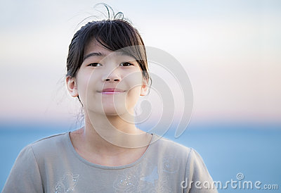 Beautiful young preteen girl enjoying outdoors by lake at sunset